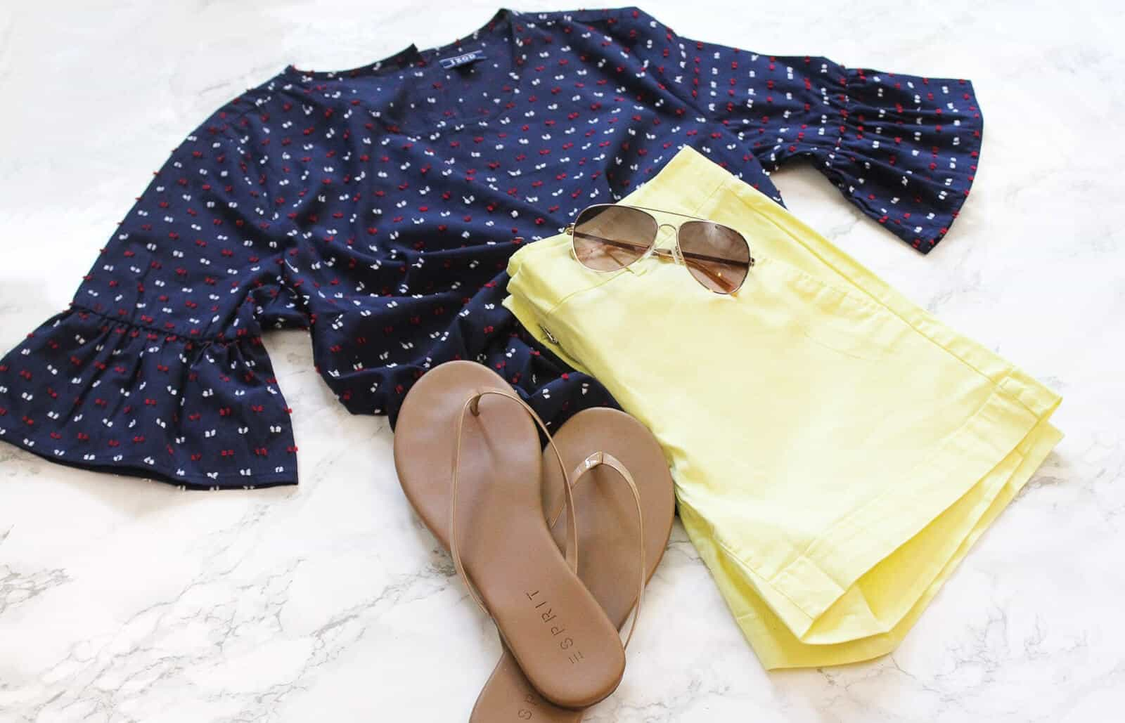 Summer outfit lays next to flip flops and sunglasses.