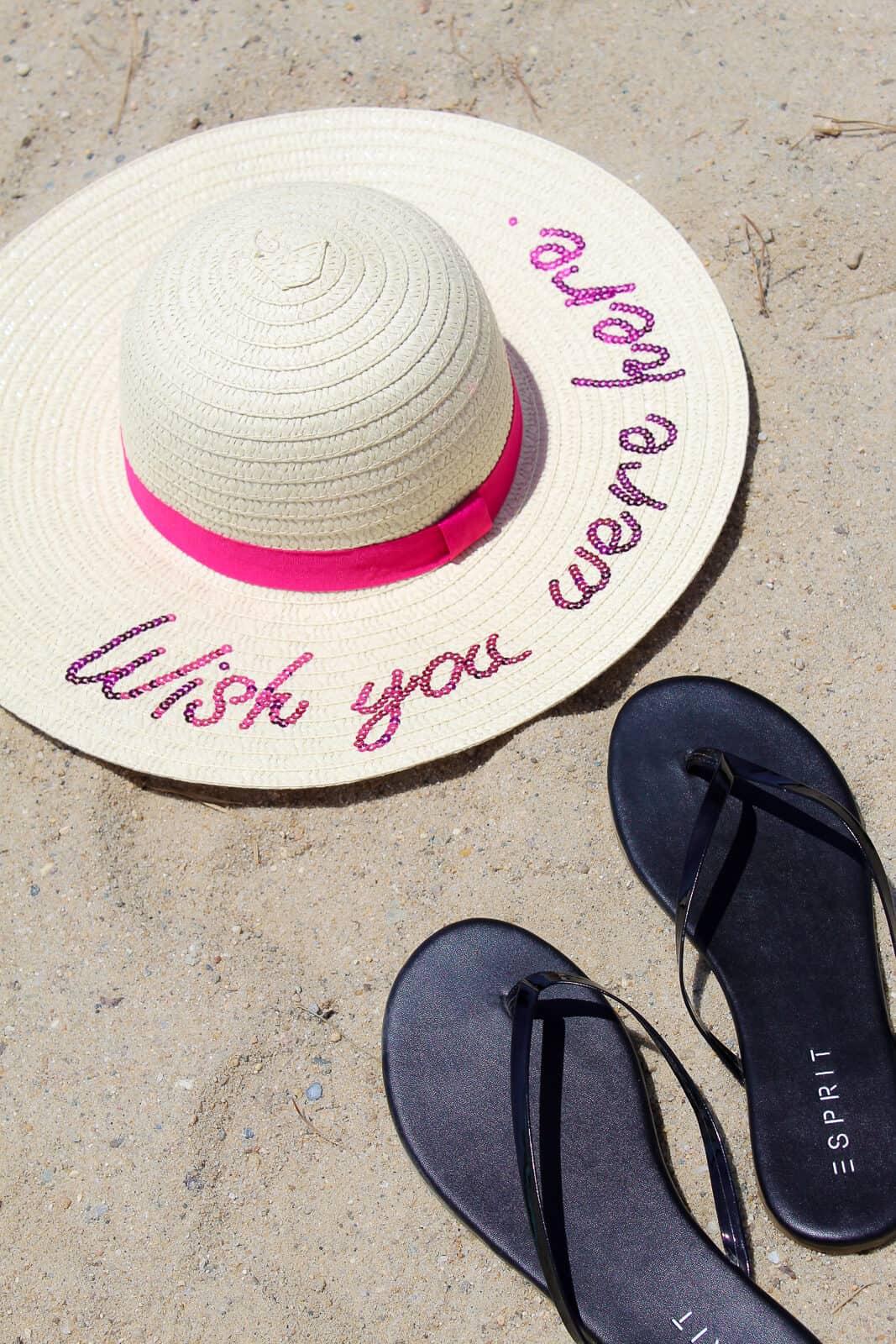Wish you were here summer hat lays on beach next to black flip flops.