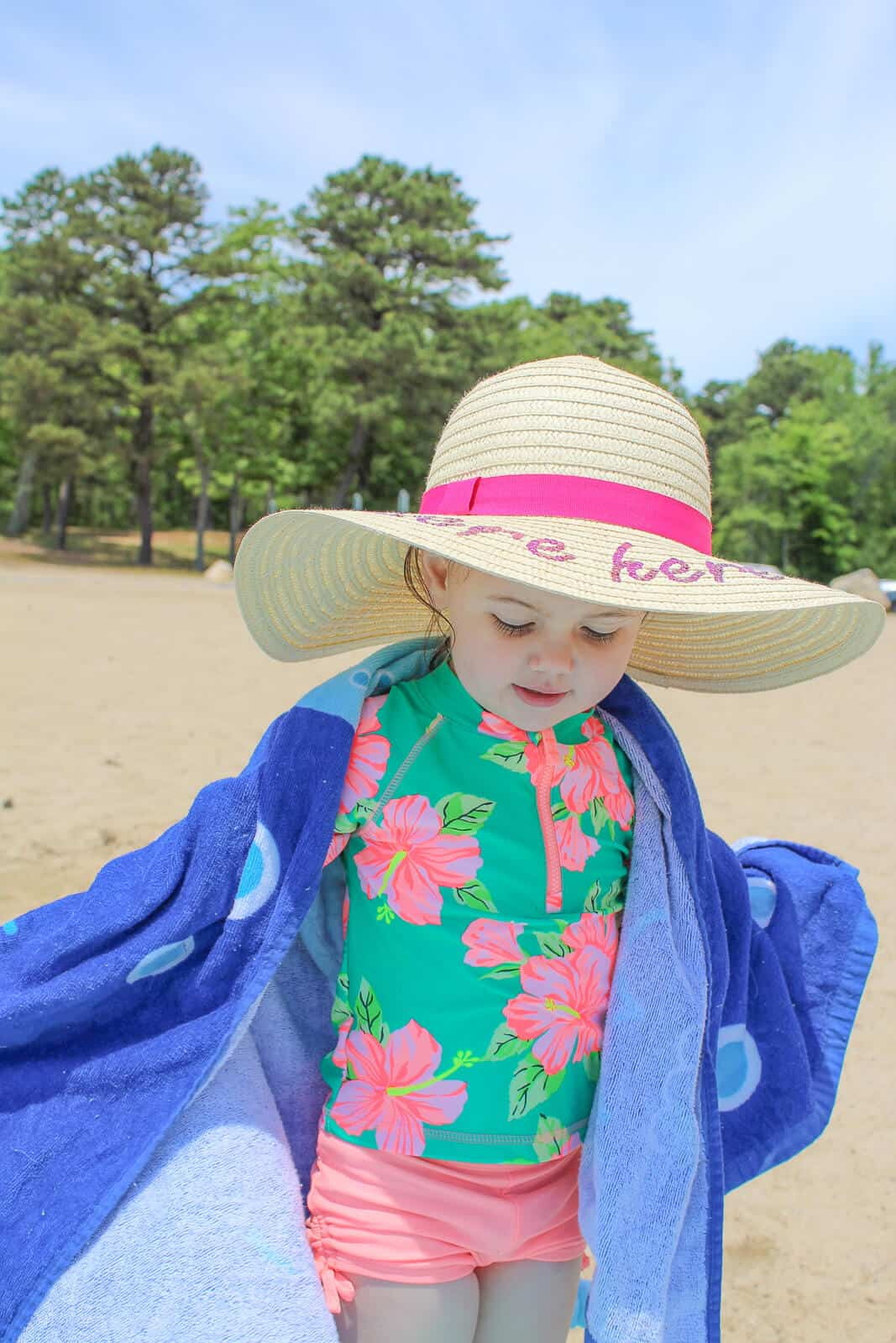Baby wears large summer hat at beach.