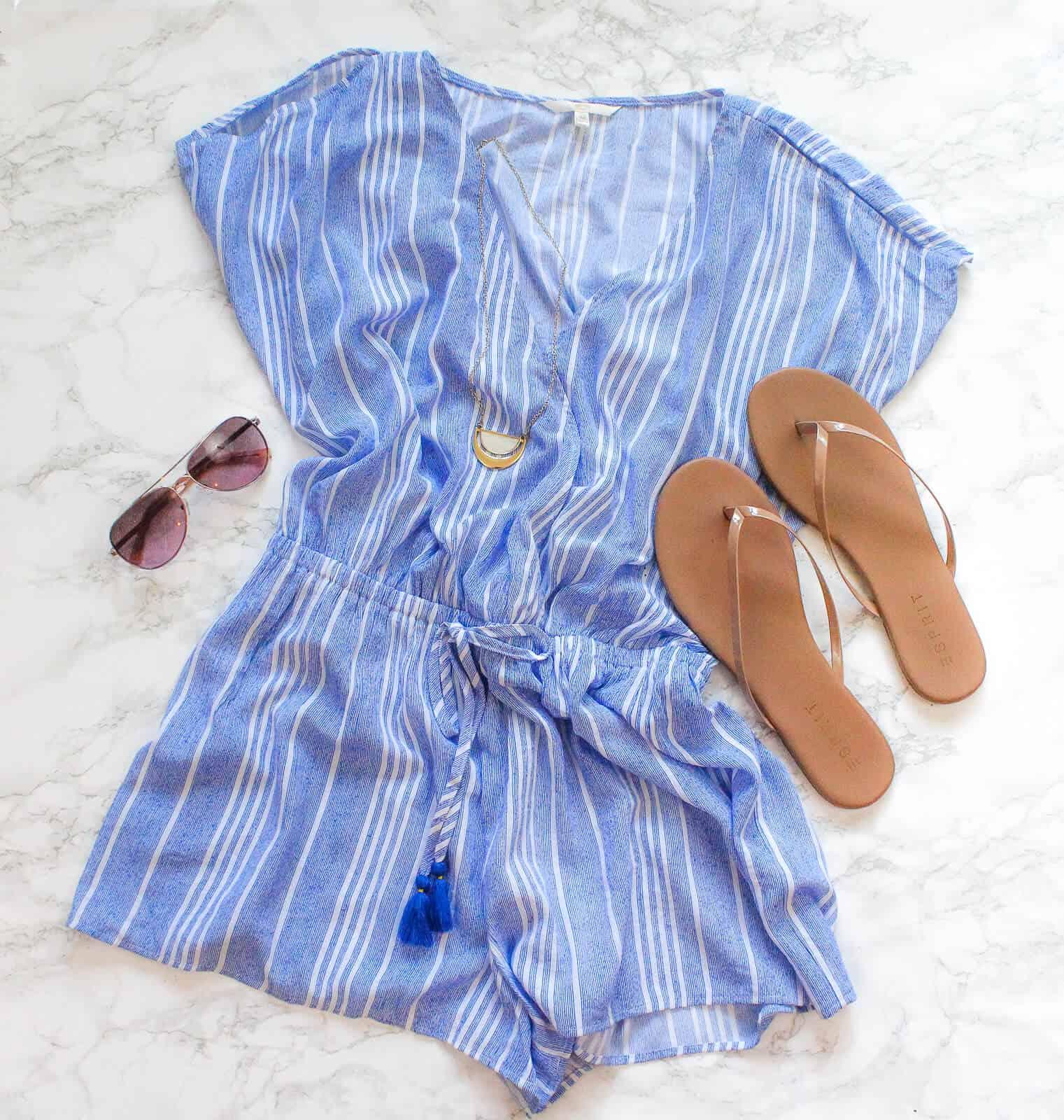 Blue summer dress next to flip flops and sunglasses.