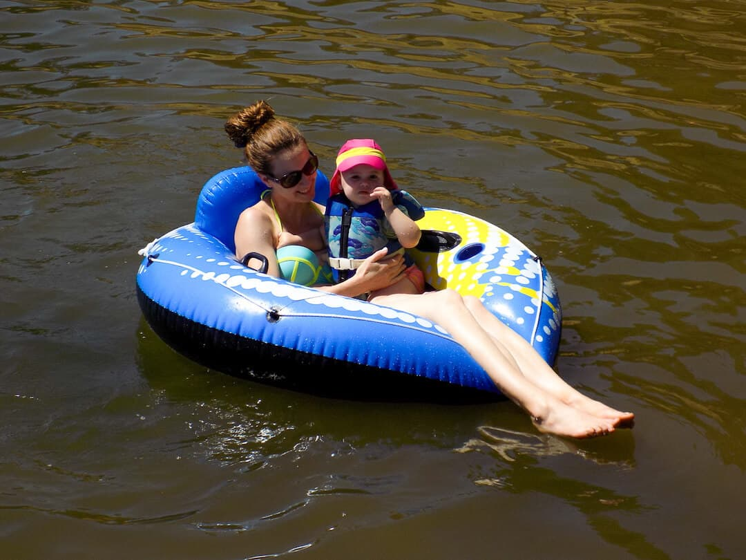 Mother and daughter float on tube in lake.