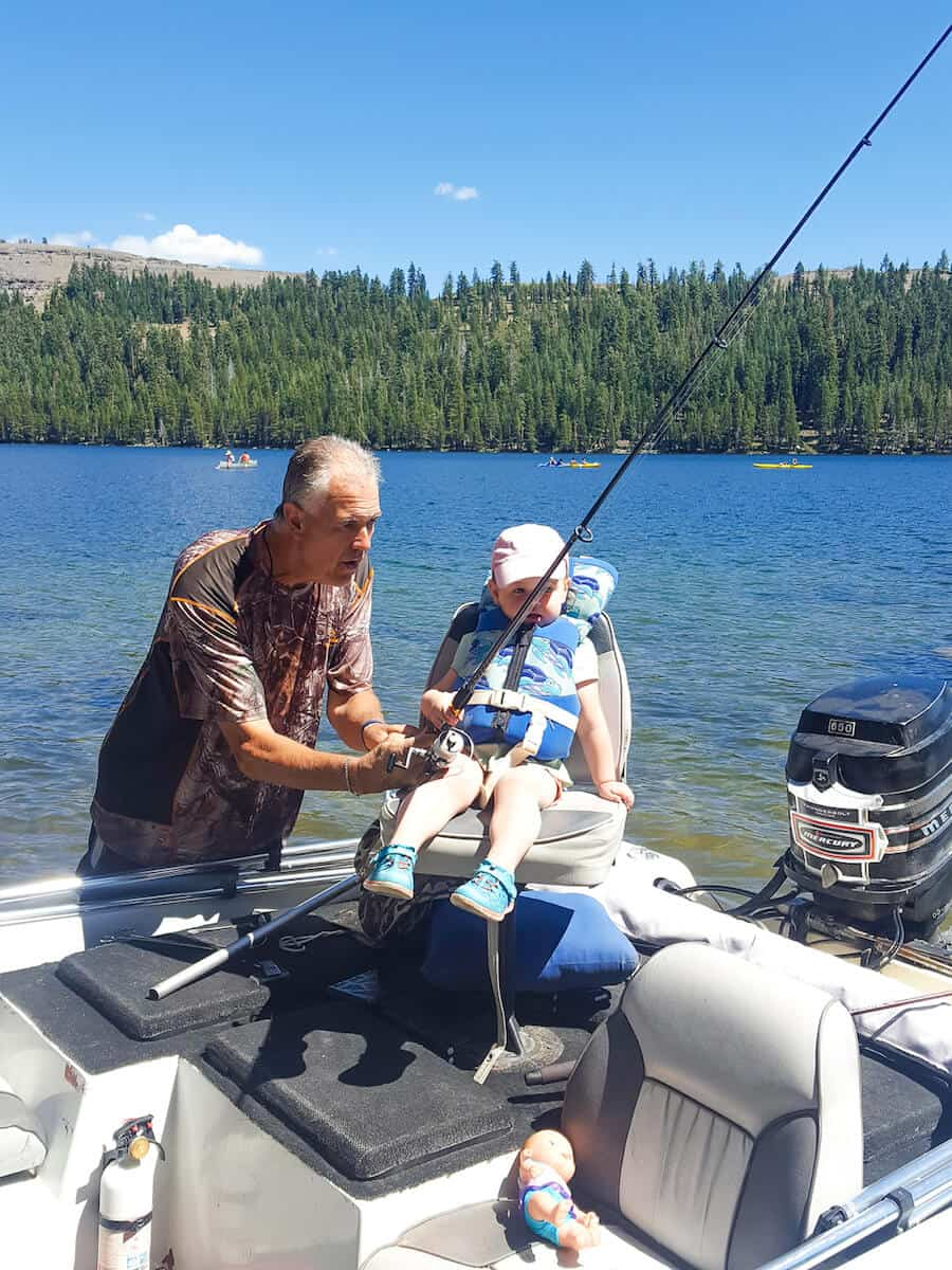 Man helps toddler girl hold fishing pole in boat.