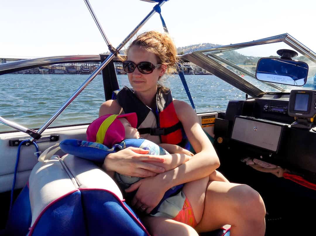 Mother holds baby girl while boating.
