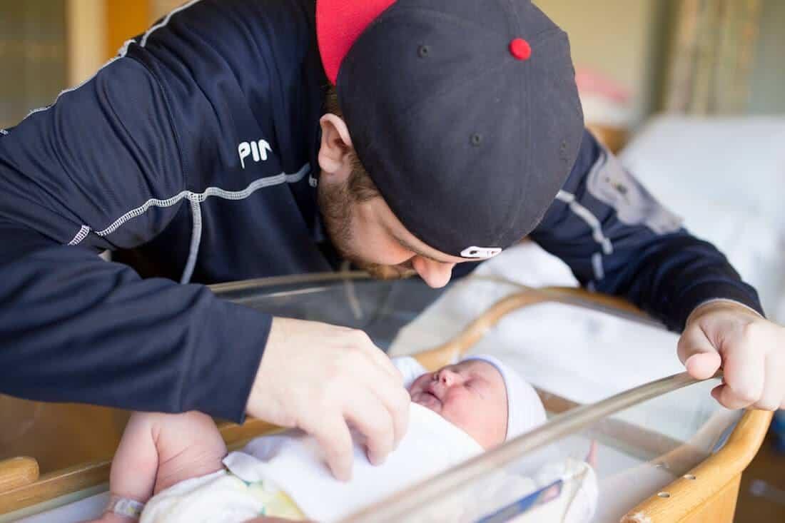 Man looks over newborn baby in hospital bassinet.