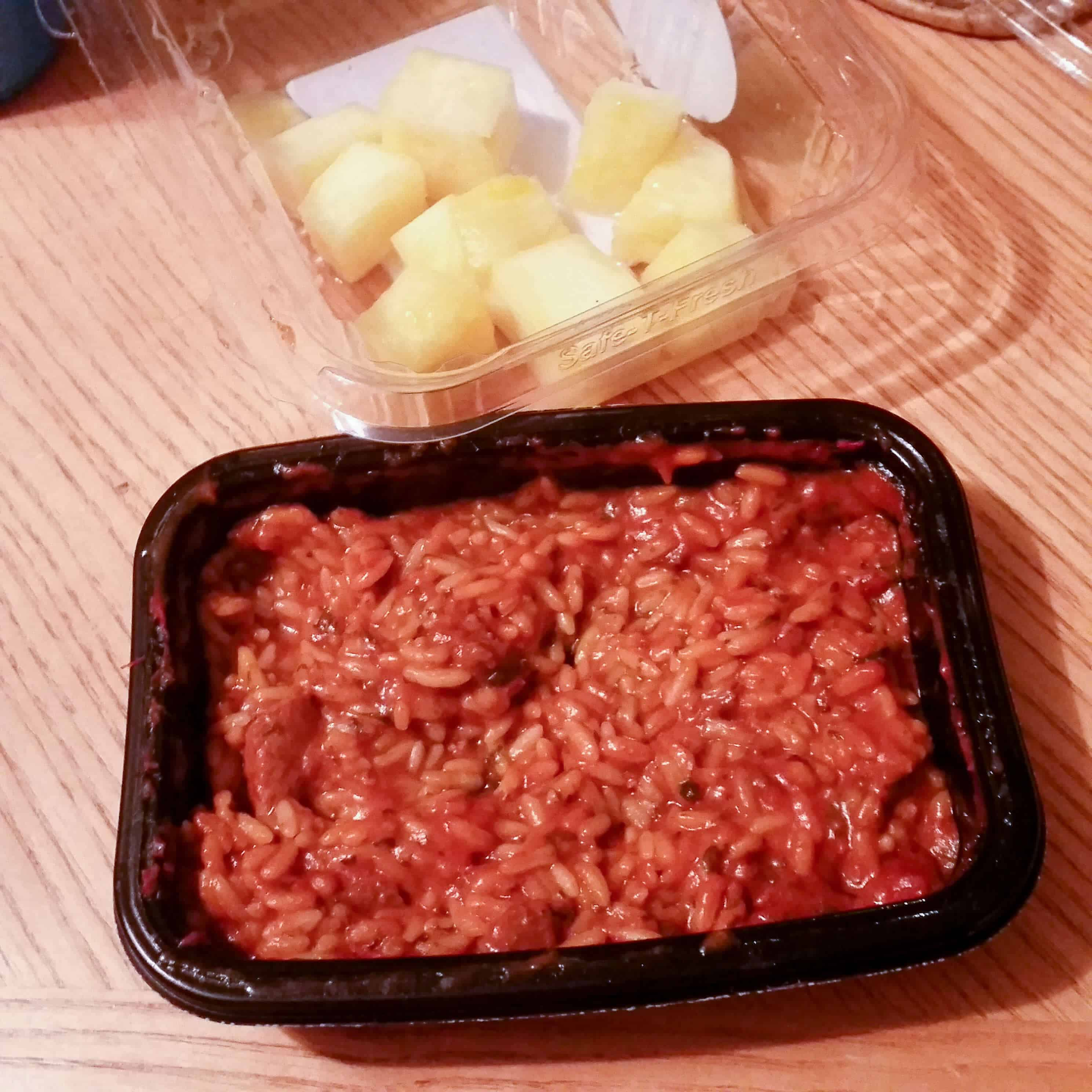 Spicy food next to container of pineapple chunks.