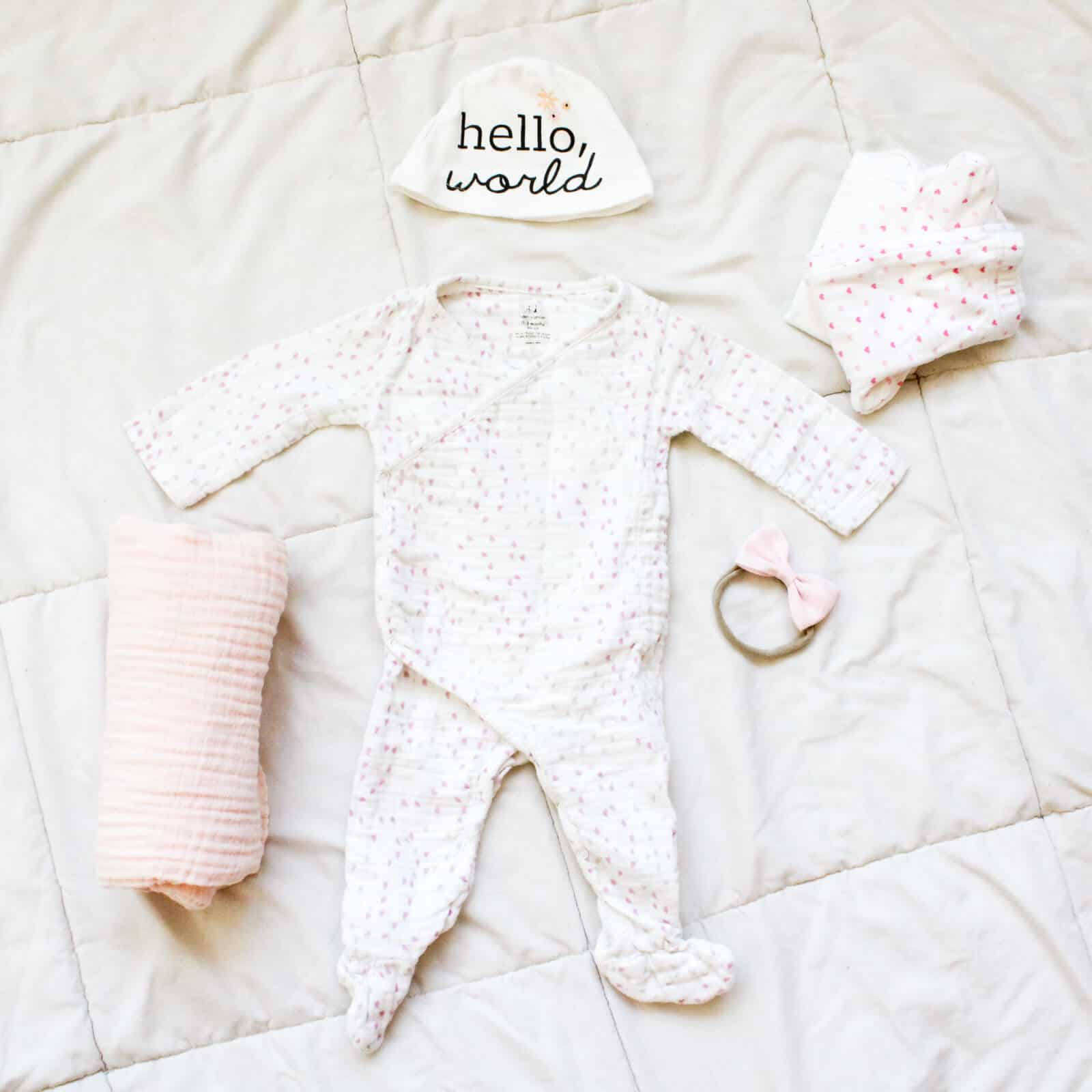 Newborn baby outfit and blanket on bed.