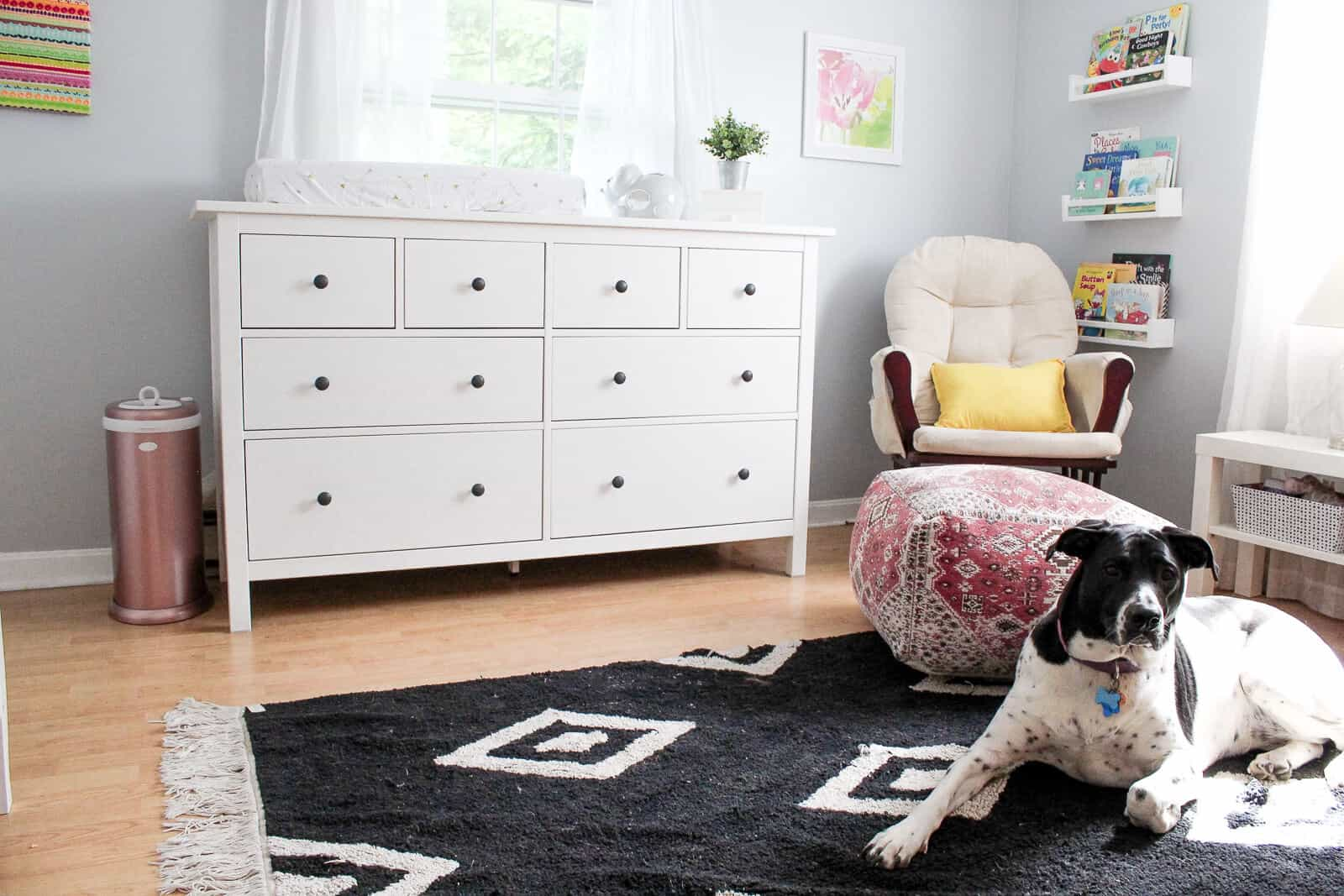 View of dresser and glider in modern baby girl bedroom.