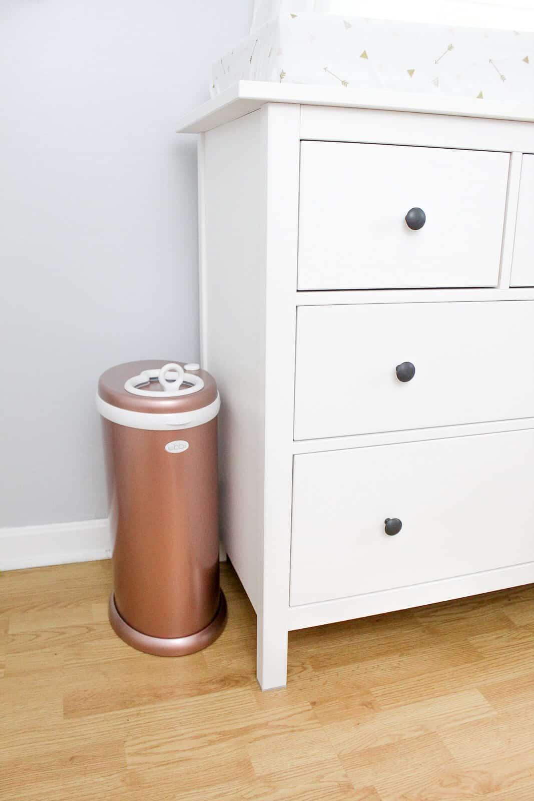 Golden diaper pail next to white dresser.