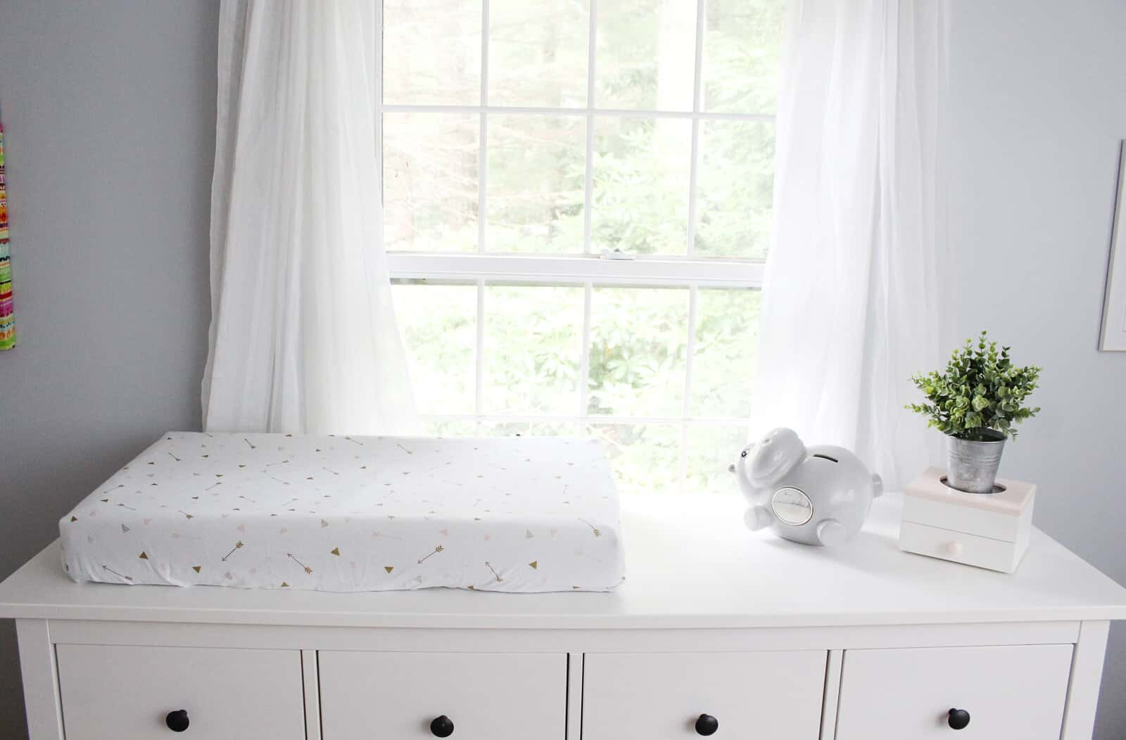 Baby changing pad on white dresser.