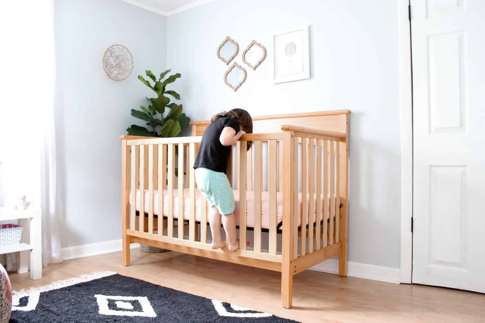 Toddler girl climbs into crib in nursery room.