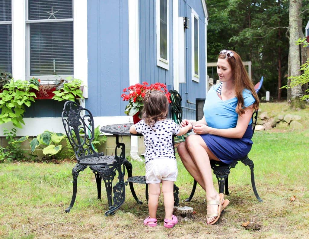 Mother sits with baby and toddler outdoors.