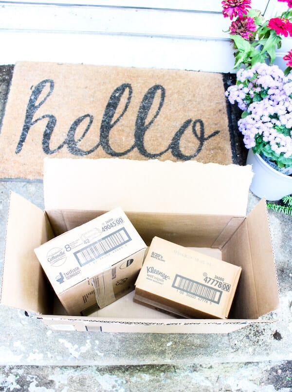 """Amazon packages on doorstep next to \""""Hello\"""" welcome mat."""