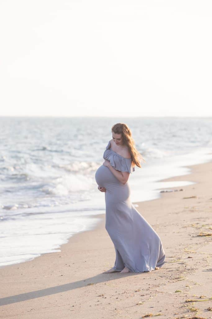 Woman wears flowy maternity dress for pictures on beach.