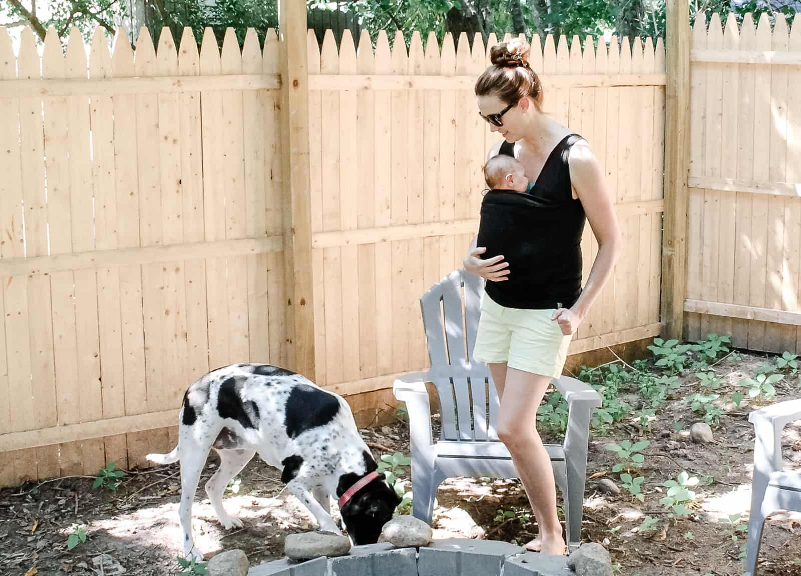 Woman wears baby in sling while outdoors with family dog.