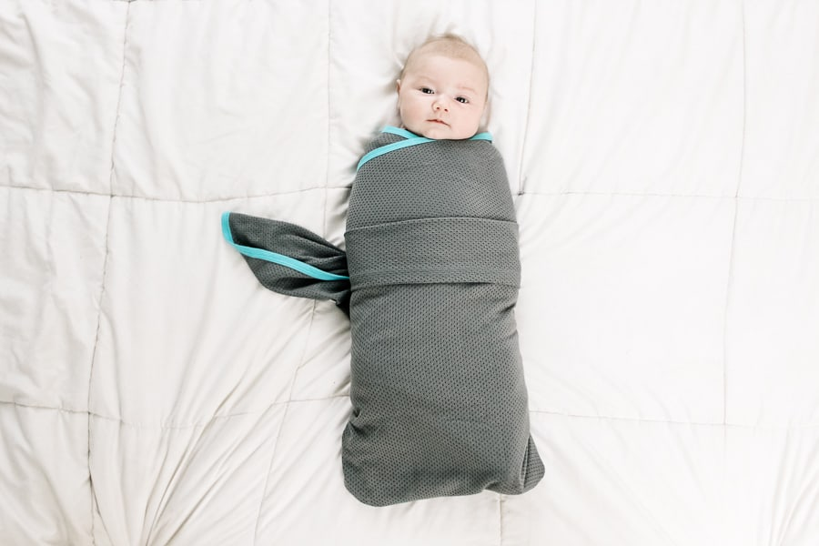 Baby lays on bed in swaddle for tutorial.