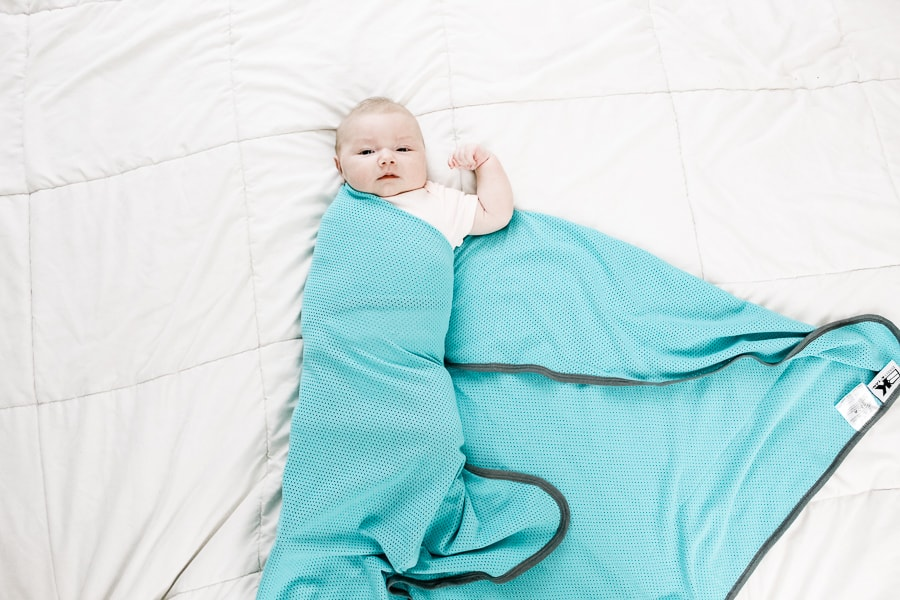 step 3 of how to swaddle a baby: fold the swaddle blanket over the baby
