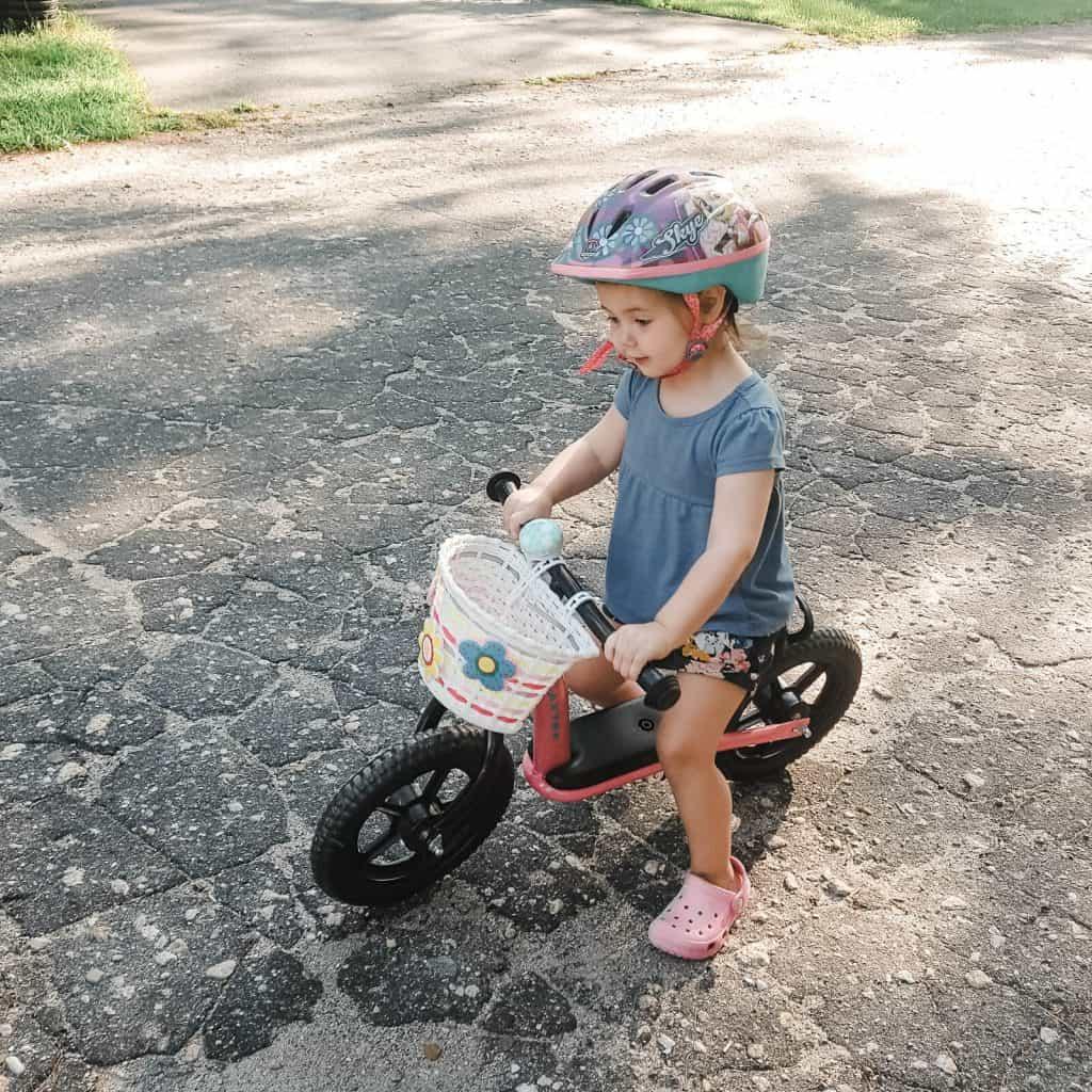 Toddler girl on bicycle.