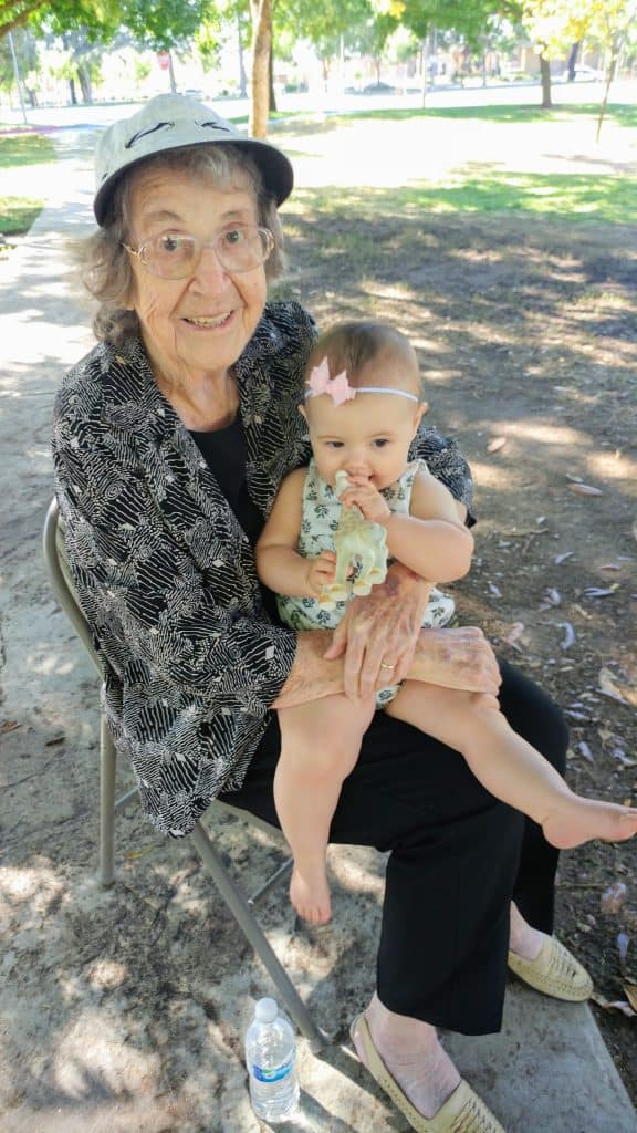 Elderly woman holds baby girl on chair outside.