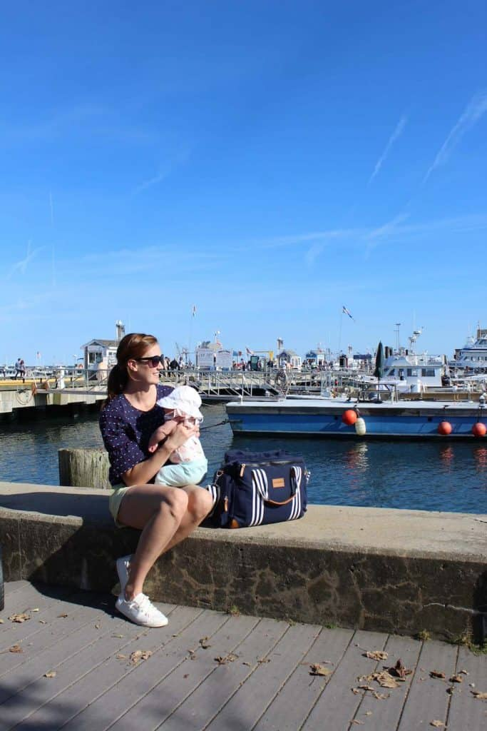 Mom sits with baby on dock in Provincetown.