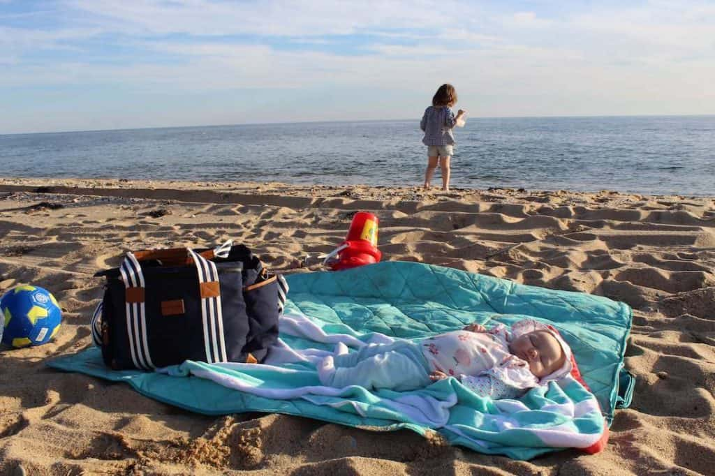 Baby sleeps on blanket on beach with toddler girl playing in background.