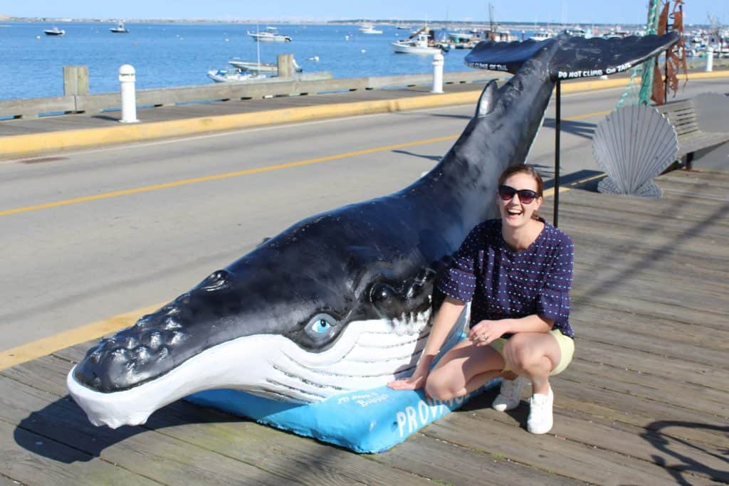 Woman poses next to fake whale in Provincetown, MA.