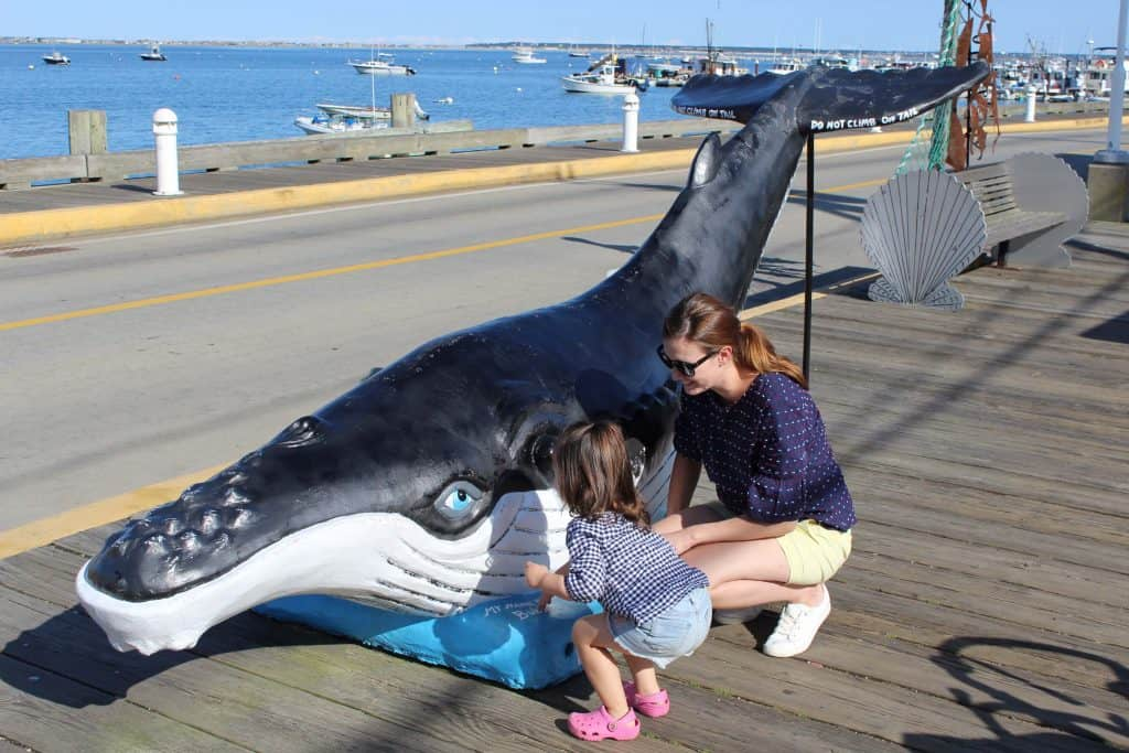 Woman and toddler girl play at whale statue.