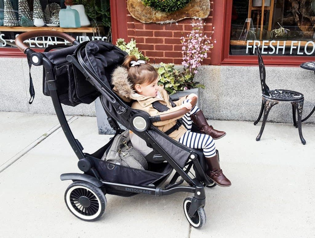 Toddler girl sits in travel stroller outside shops.