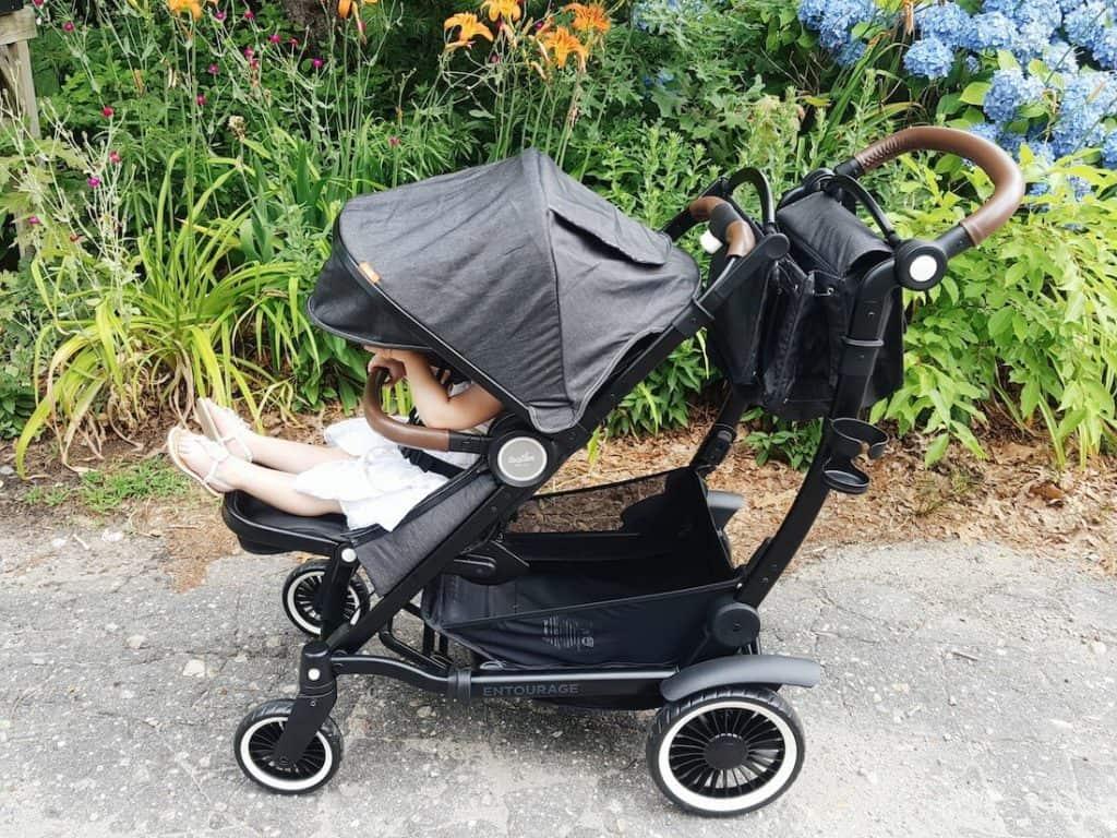 Little girl sits in stroller on walking path.