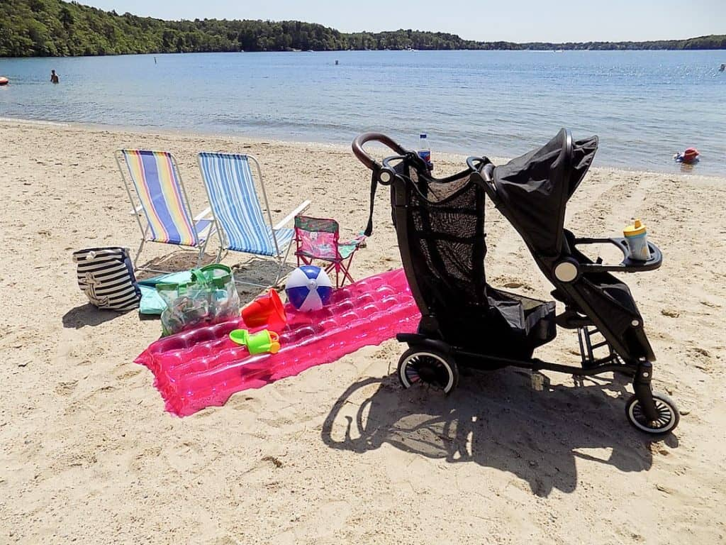 Stroller on beach next to chairs and float.