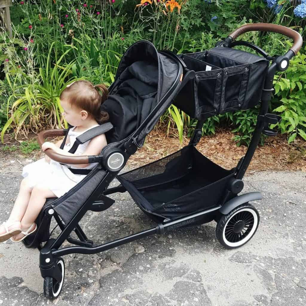 Child sits in double stroller at Disney park.