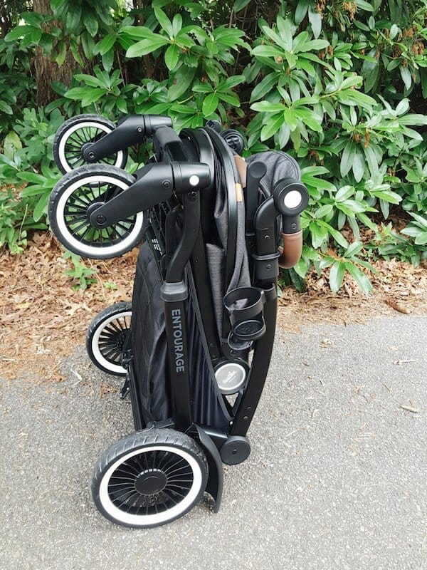 Stroller is folded together on walking path.