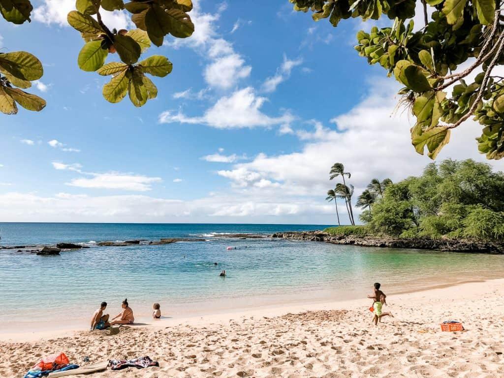 People play on a hidden beach in Oahu.