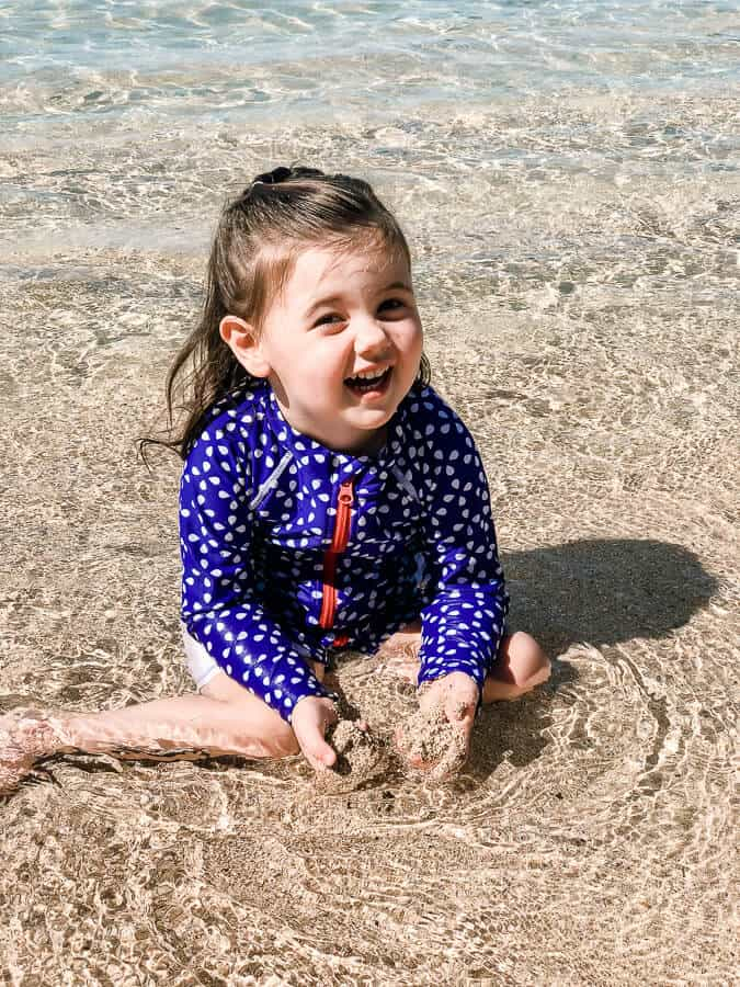 Little girl plays in water at beach.