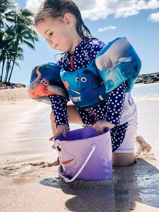 Girl plays with bucket at hidden beach in Hawaii.