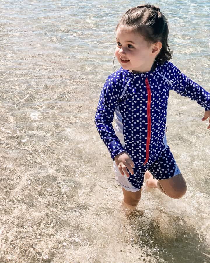 Girl plays in ocean at Hawaii family beach.