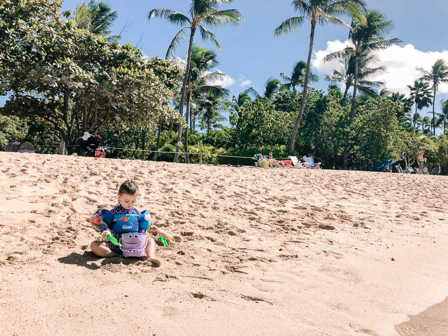 Girl plays in the sand at Family beach in Oahu.