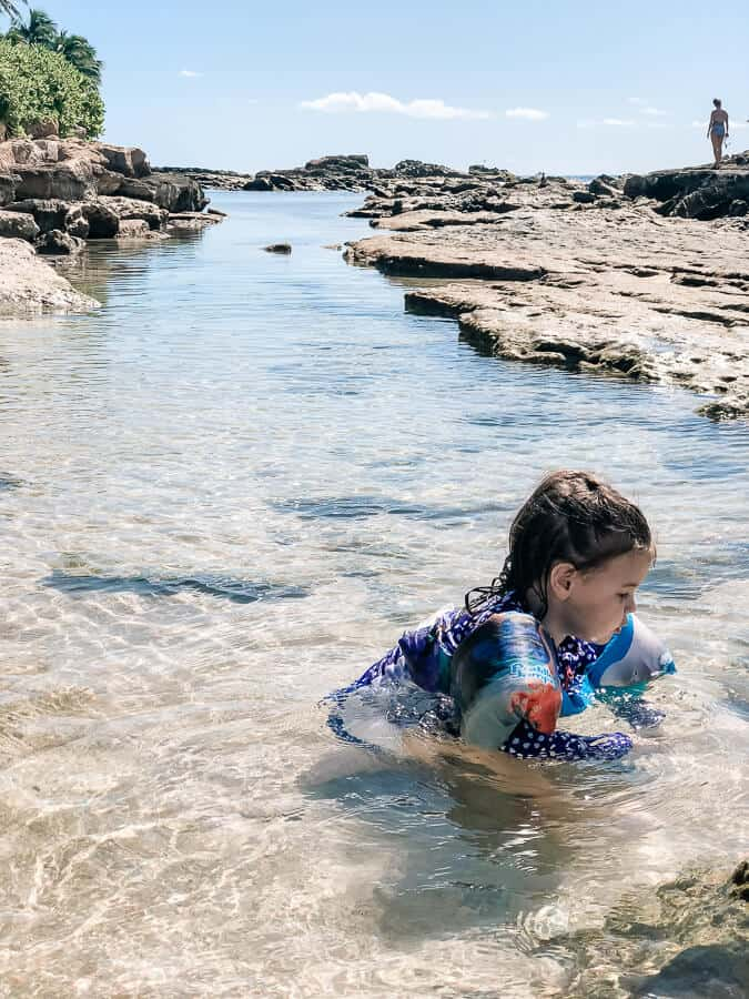 Girl plays in water channel at Oahu beach for families.