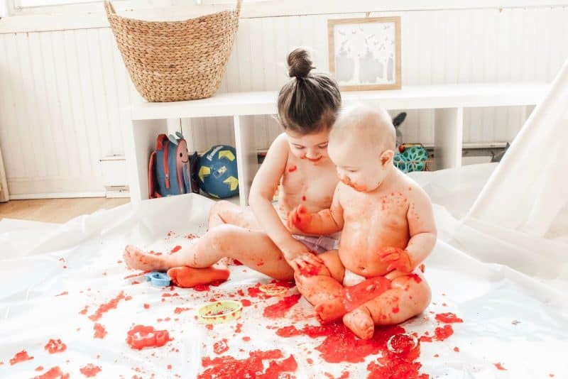 Baby and toddler making a mess with jello during sensory play