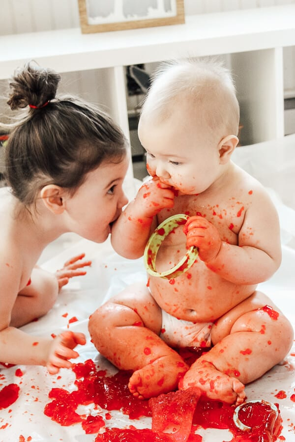 Toddler and baby eat red Jello during play time.