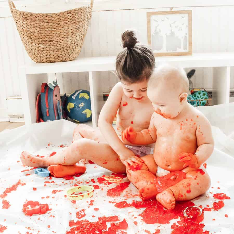 Children use red Jello for sensory play.