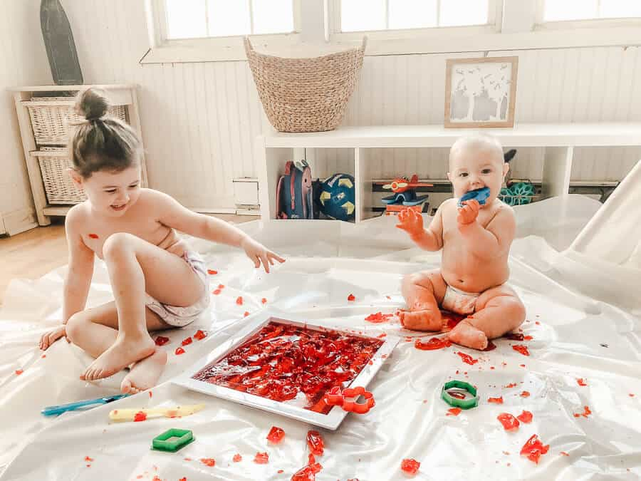 Young girl and baby play with red Jello over drop cloth.