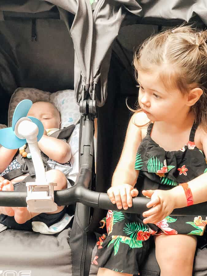 Toddler and baby in double stroller at Disney park.