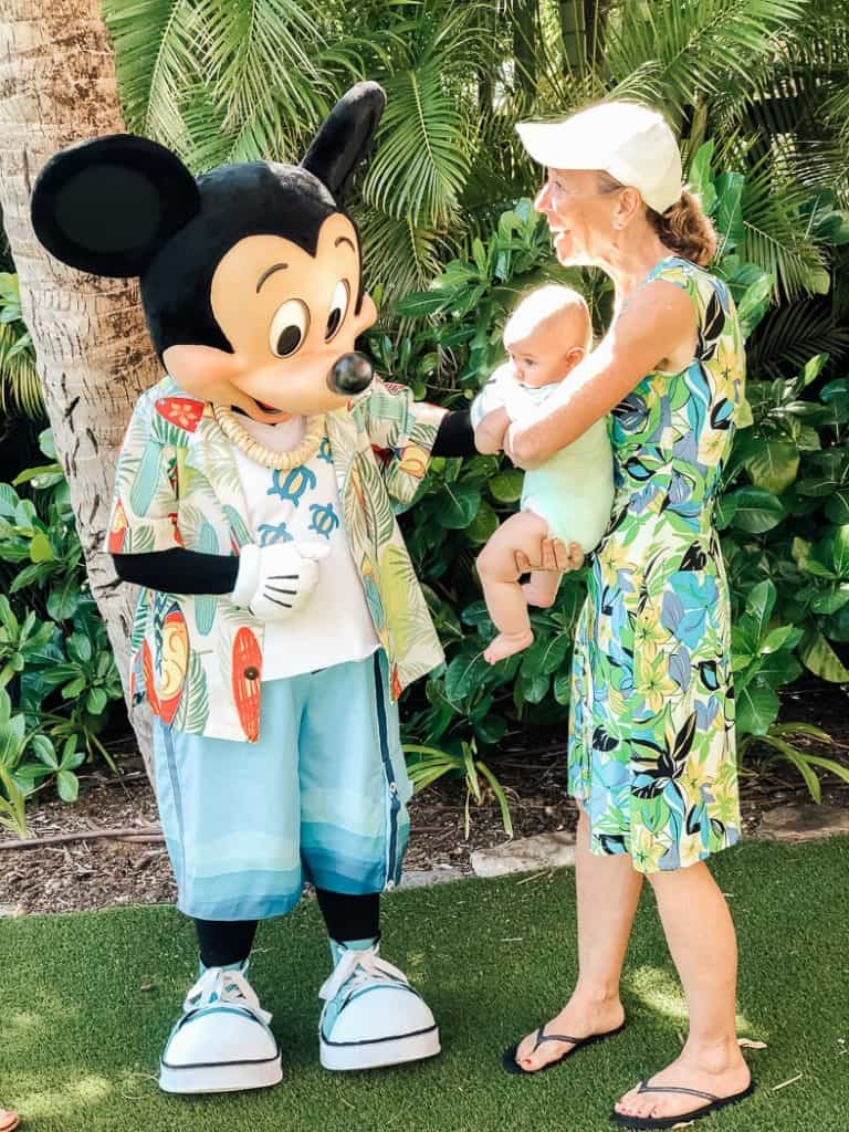 Mom introduces baby to Mickey Mouse at Hawaii resort.