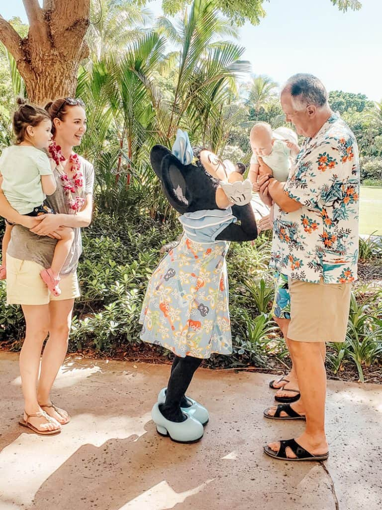 Family interacts with Mini Mouse at Disney park.