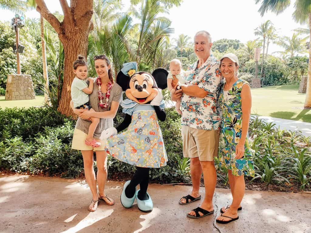 Family poses with Mini Mouse at Disney Aulani Resort.
