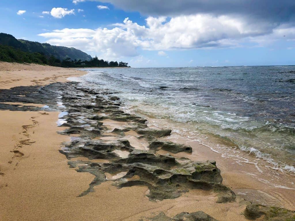 A sandy beach next to ocean in Oahu.
