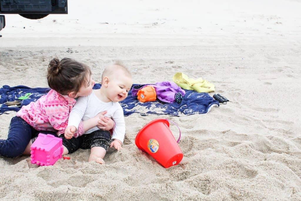 Toddler girl and baby play at beach.