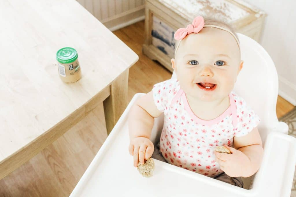 Baby eats baby food muffins in high chair.