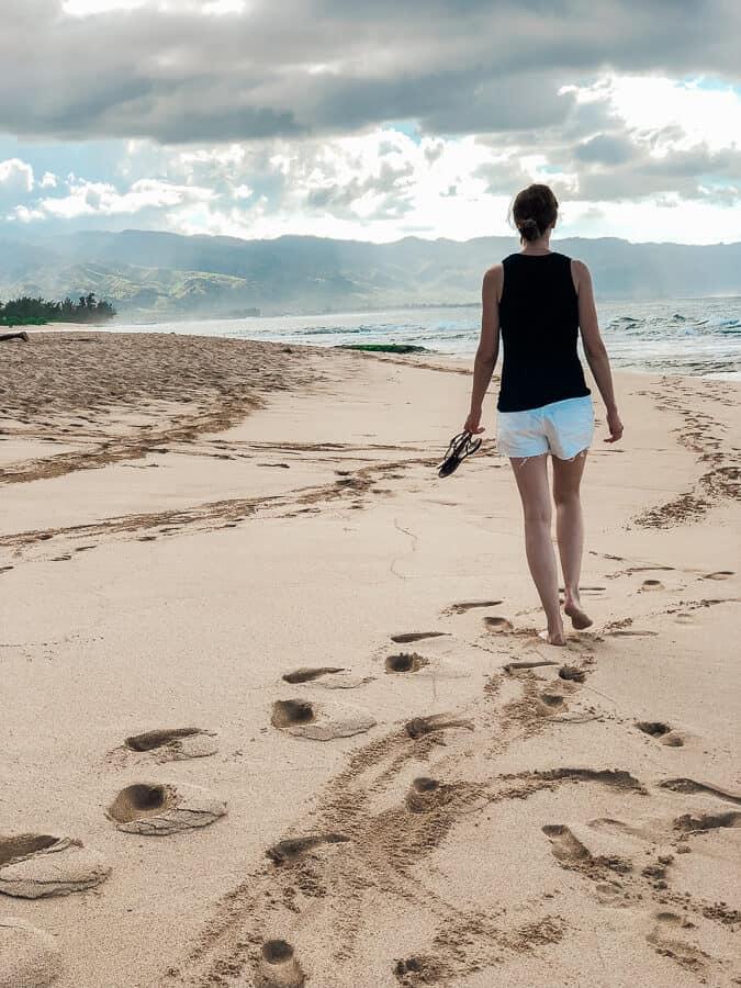 Woman walks on beach in Oahu Hawaii.