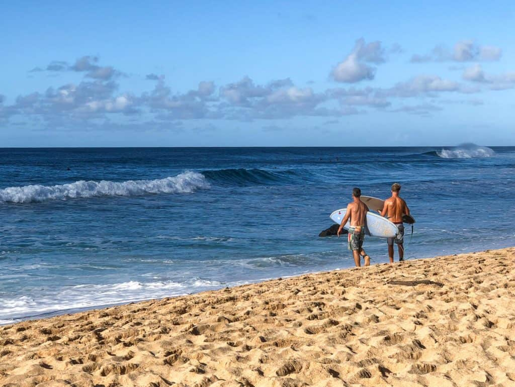 Surfers on beach in North Shore Hawaii.